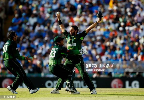 Captain Shahid Afridi of Pakistan celebrates with team mates Kamran Akmal and Saeed Ajmal after taking the catch to dismiss Sachin Tendulkar of India...