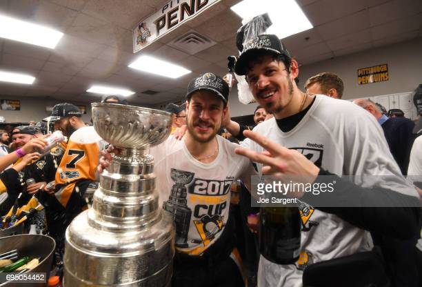Captain Sidney Crosby and Evgeni Malkin of the Pittsburgh Penguins pose for a photo with the Stanley Cup in the locker room after Game Six of the...