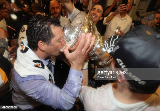 Captain Sidney Crosby of the Pittsburgh Penguins helps former Penguins player Bill Guerin with a drink from the Stanley Cup in the locker room after...