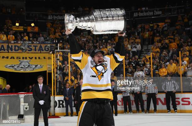 Captain Sidney Crosby of the Pittsburgh Penguins lifts the Stanley Cup over his head after Game Six of the 2017 NHL Stanley Cup Final at the...