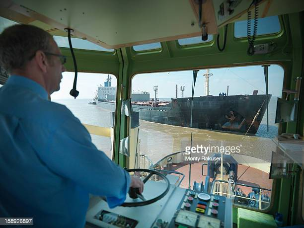 Captain steering in bridge of tugboat towing ship at sea