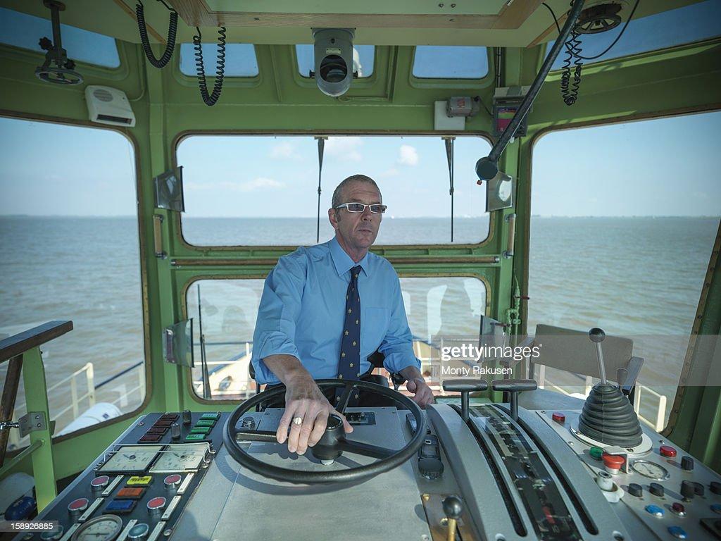 captain steering in wheelhouse of tugboat at sea stock photo