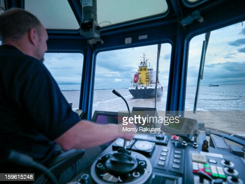 Captain steering tug out at sea view of ships bridge and tug seen through window