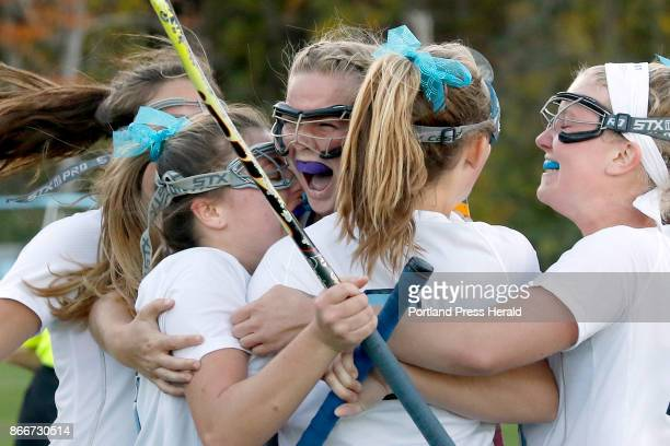 Captain Sydney Bouchard center is swarmed by her York teammates after scoring the winning goal in double overtime against Lake Region securing the...