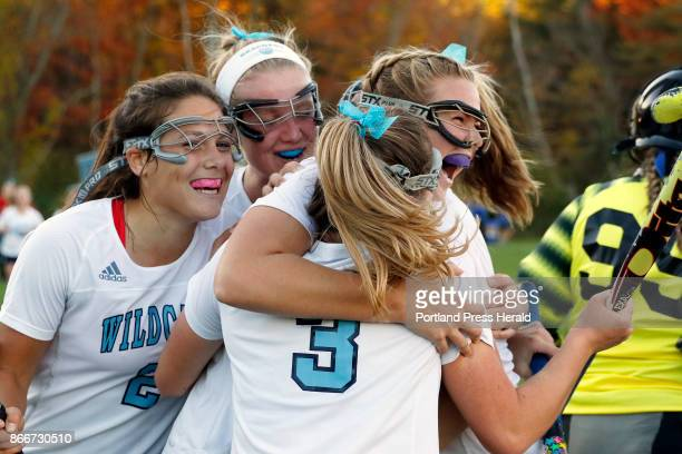 Captain Sydney Bouchard right is swarmed by her York teammates after scoring the winning goal in double overtime against Lake Region securing the...