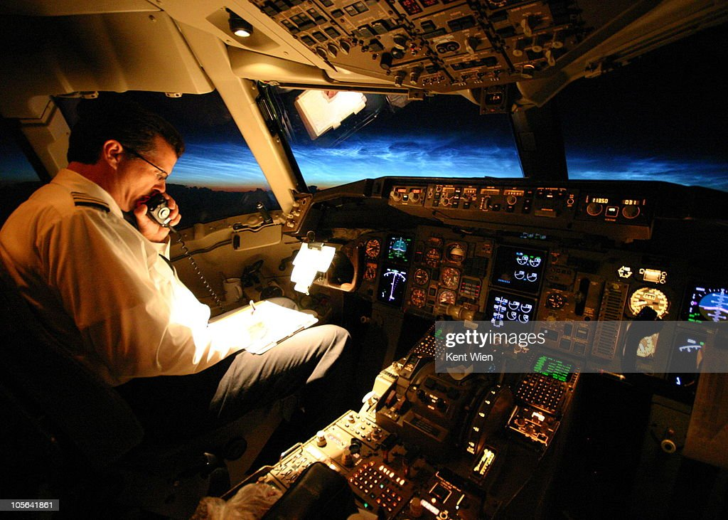 Captain talking to ATC with sunrise behind : Stock Photo