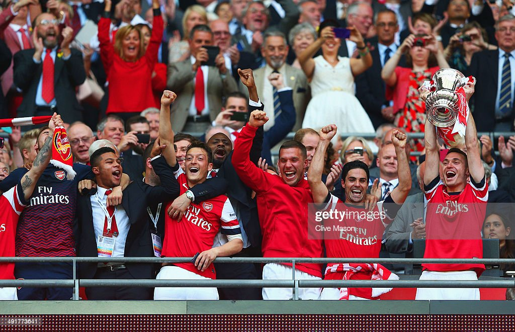 Captain Thomas Vermaelen of Arsenal (R) lifts the trophy in celebration after the FA Cup with Budweiser Final match between Arsenal and Hull City at Wembley Stadium on May 17, 2014 in London, England.