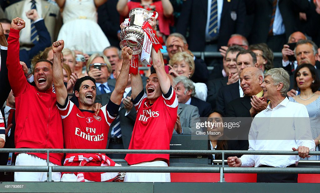 Captain Thomas Vermaelen of Arsenal (2R) lifts the trophy in celebration alongside Lukas Podolski (L), Mikel Arteta (2L) and Arsene Wenger manager of Arsenal (R) after the FA Cup with Budweiser Final match between Arsenal and Hull City at Wembley Stadium on May 17, 2014 in London, England.