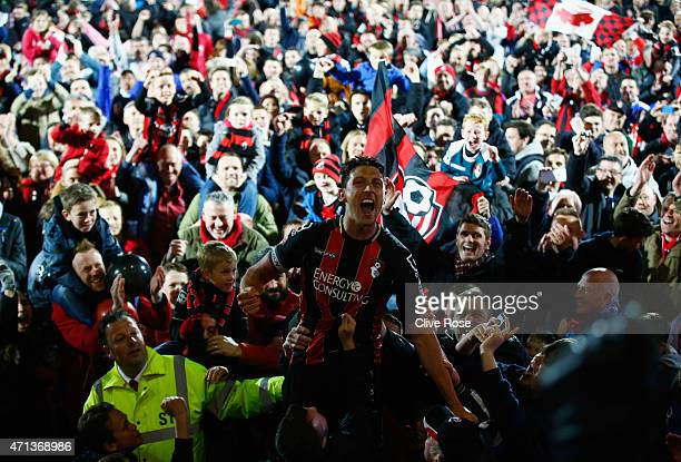 Captain Tommy Elphick of Bournemouth celebrates victory as fans invade the pitch after the Sky Bet Championship match between AFC Bournemouth and...
