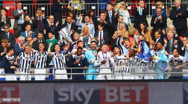 Captain Tony Craig of Millwall lifts the trophy as he celebrates victory and promotion with team mates after the Sky Bet League One Playoff Final...
