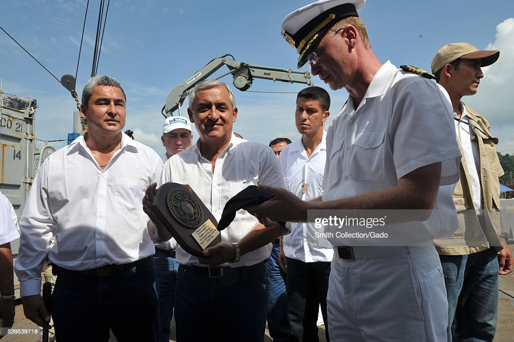 Captain Troy Bruemmer presents the president of Guatemala, Otto Pérez Molina, a plaque from the Military Sealift Command rescue and salvage ship USNS Grapple T-ARS 53 during his visit to meet Sailors assigned to Mobile Diving and Salvage Unit MDSU 2, Company 2-1, Puerto Barrios, Guatemala, 2012. Image courtesy Mass Communication Specialist 2nd Class Kathleen A. Gorby/US Navy. (Photo by Smith Collection/Gado/Getty Images).