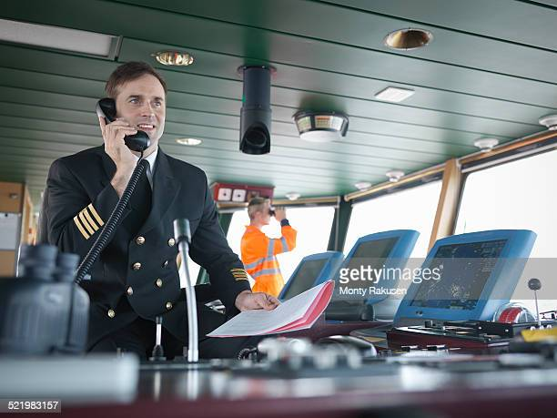 Captain using telephone on bridge of ship