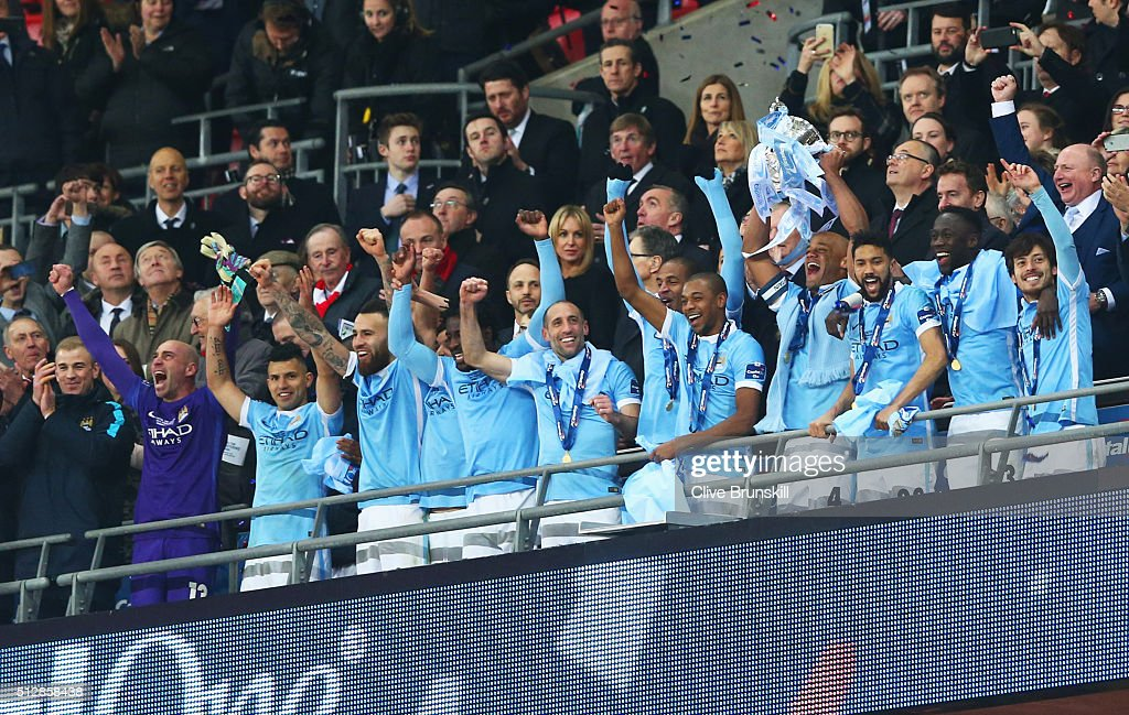 Captain Vincent Kompany of Manchester City lifts the trophy with team mates in celebration after the Capital One Cup Final match between Liverpool and Manchester City at Wembley Stadium on February 28, 2016 in London, England. Manchester City win 3-1 on penalties.