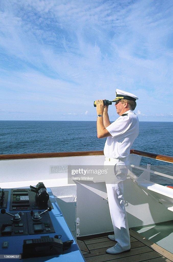 Captain w/ binoculars on bridge of cruise ship