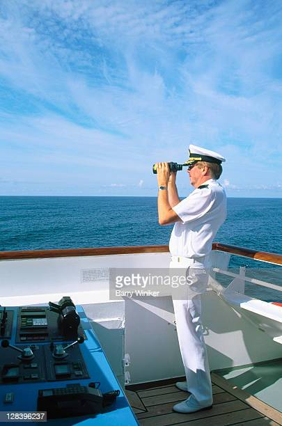 Captain w/ binoculars on bridge of cruise ship