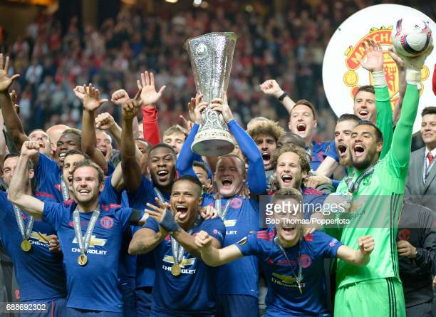 Captain Wayne Rooney holds aloft the trophy and celebrates with the Manchester United team after the UEFA Europa League final between Ajax and...
