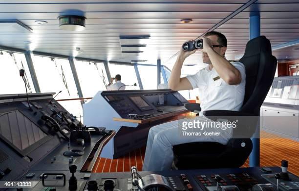 Captain with binoculars on the bridge of an Aida cruise ship in the Baltic Sea on July 02 in Baltic Sea Germany AIDA Cruises is a BritishAmerican...