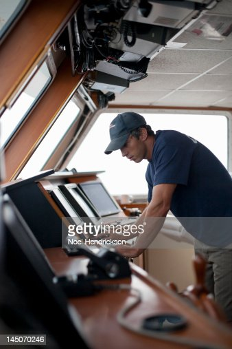 A captain working at the bridge of a boat : Stock Photo