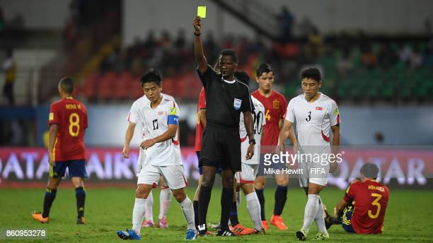 Captain Yun Min of Korea DPR receives a yellow card from referee Jose Argote of Venezuela during the FIFA U17 World Cup India 2017 group D match...