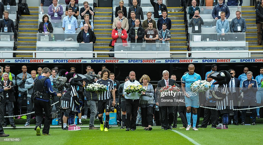 Captains <a gi-track='captionPersonalityLinkClicked' href=/galleries/search?phrase=Fabricio+Coloccini&family=editorial&specificpeople=469707 ng-click='$event.stopPropagation()'>Fabricio Coloccini</a> of Newcastle (L) and Vincent Komany of Manchester city (R) walk on the pitch holding wreaths with family members of the two men (John Alder and Liam Sweeney) who lost their lives on flight MH17 during the Barclays Premier League match between Newcastle United and Manchester City at St.James' Park on August 17, 2014, in Newcastle upon Tyne, England.