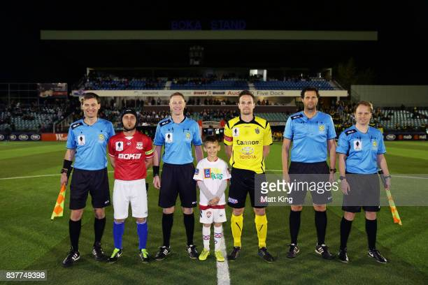 Captains Nicholas Stavroulakis of Sydney United 58 FC and Luke Byles of Heidleberg United pose with referees after the coin toss during the FFA Cup...