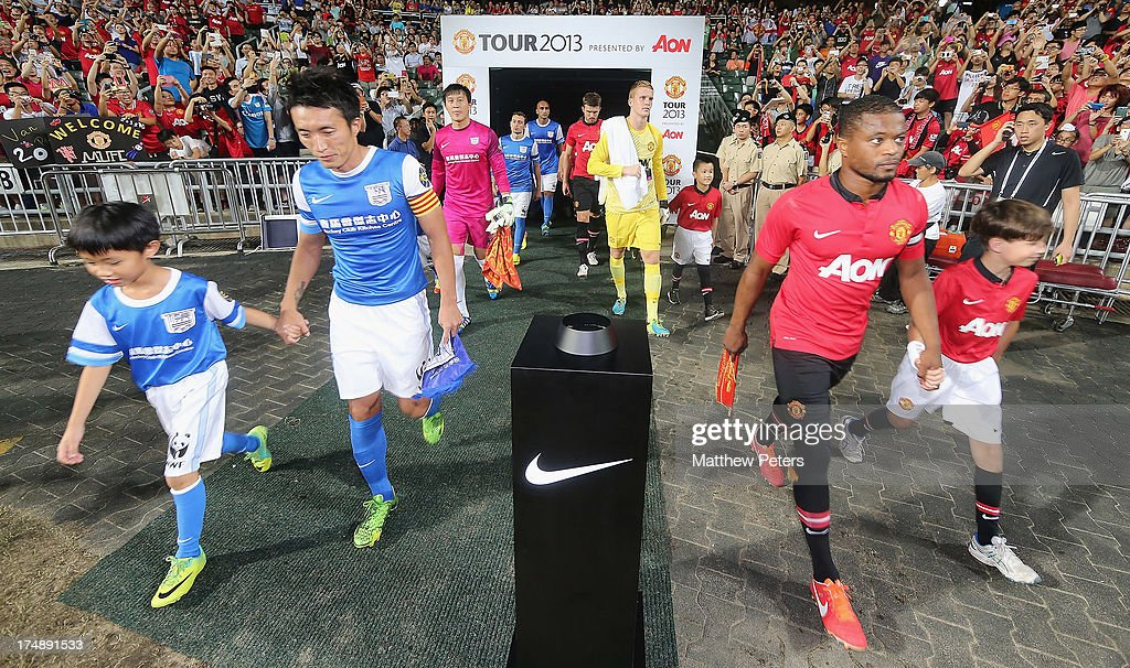 Captains Patrice Evra of Manchester United and Chu of Kitchee FC lead the two teams out ahead of the pre-season friendly match between Kitchee FC and Manchester United as part of their pre-season tour of Bangkok, Australia, Japan and Hong Kong at Hong Kong Stadium on July 29, 2013 in So Kon Po, Hong Kong.