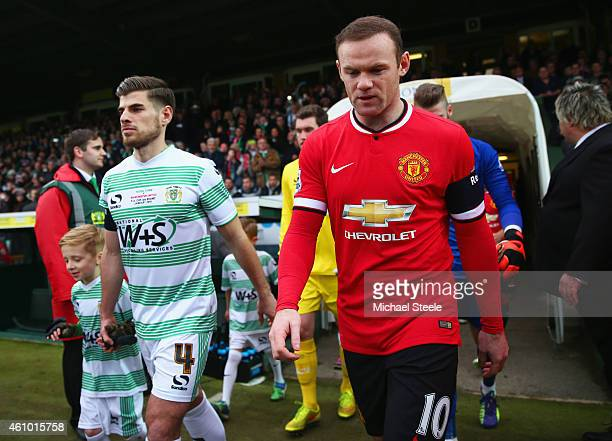 Captains Sam Hoskins of Yeovil Town and Wayne Rooney of Manchester United lead out the teams prior to the FA Cup Third Round match between Yeovil...