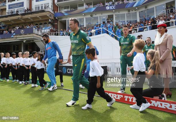 Captain's Virat Kohli of India and AB de Villiers of South Africa lead their teams out during the ICC Champions Trophy Group B match between India...
