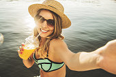Capturing every happy summer moments. High-angle view of beautiful and young blonde haired woman drinking orange juice and keeping camera in hand while taking selfie on the beach.
