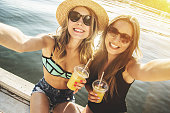 Capturing every summertime moment with friend. Two beautiful and young women taking selfie with lemonade on camera while sitting on the beach.