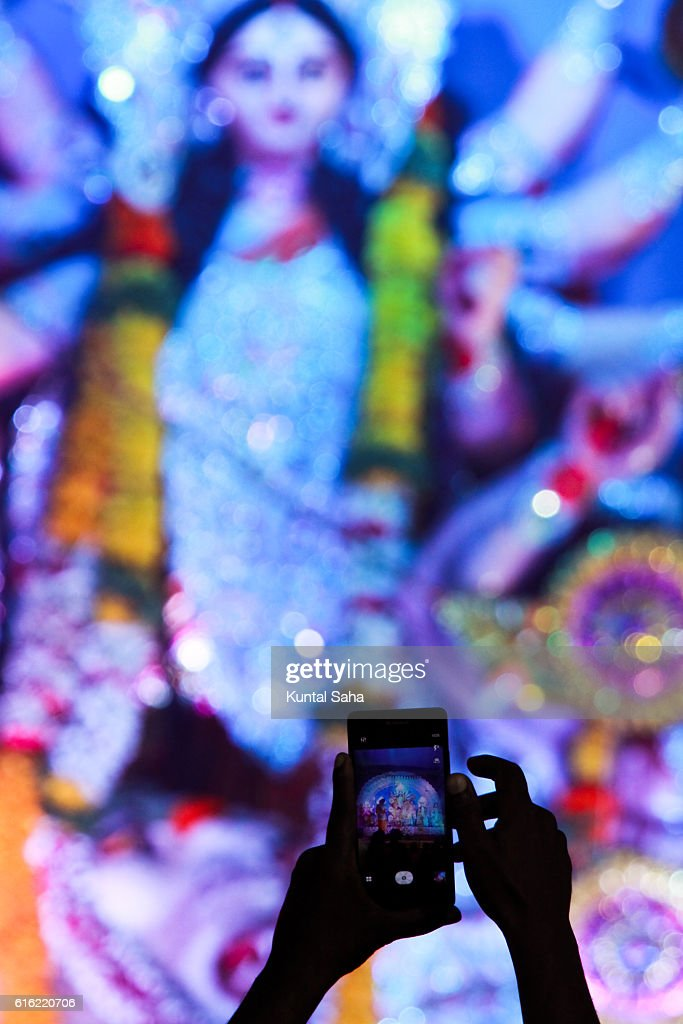 Capturing idol of goddess durga in mobile : Stockfoto