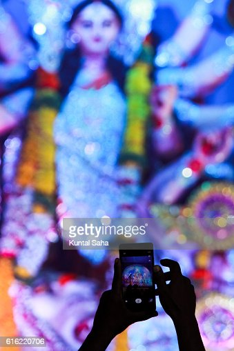Capturing idol of goddess durga in mobile : Stock Photo