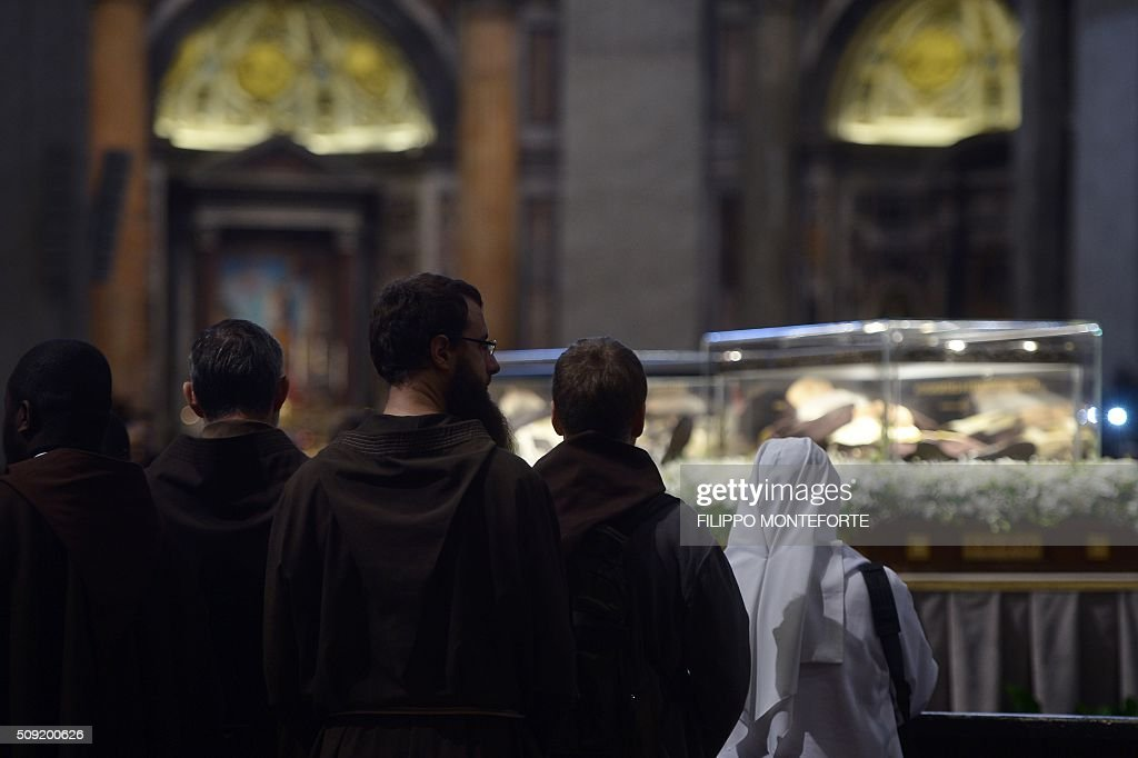 Capuchins and nuns stannd near the embalmed corpses of two Catholic saints, Italian friar Padre Pio and Leopold Mandic on February 9, 2016 at St Peter's basilica in Vatican where the saints are on display until February 11. Pio was revered during his lifetime (1887-1968) and his popularity has continued to grow since his death, particularly in Italy, where mini-statues and pictures of the mystical Capuchin friar are ubiquitous. / AFP / FILIPPO MONTEFORTE