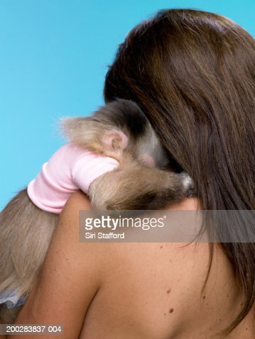 Capucine monkey (Cebus capucinus) sleeping on woman's shoulder