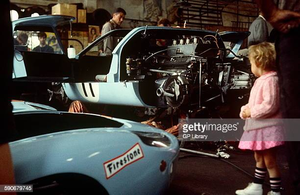Car 11 in background is Gulf JW team Ford GT40 in the team garage codriven by Brian Muir Jackie Oliver 29 September 1968