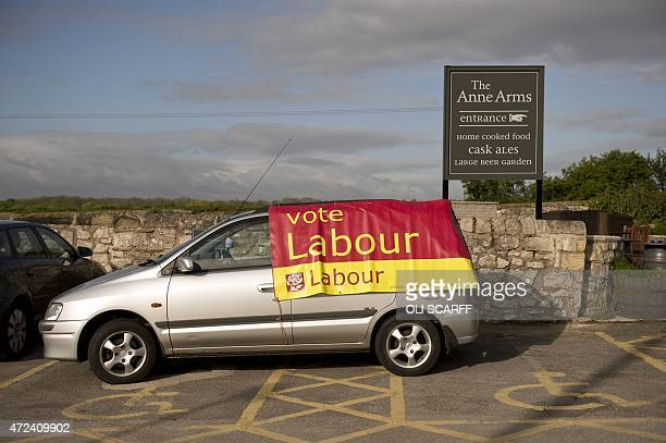 A car adorned with a poster encouraging people to vote for the Labour Party is parked across disabled parking bays outside the Anne Arms pub in the...
