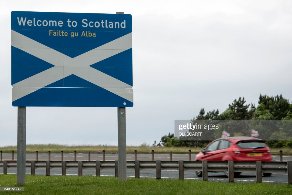 A car adorned with St George's Cross flags passes a welcome sign as it crosses the border into Scotland near Berwick-upon-Tweed in northern England close to the border between England and Scotland on June 26, 2016. Scotland's First Minister Nicola Sturgeon campaigned strongly for Britain to remain in the EU, but the vote to leave has given the Scottish National Party leader a fresh shot at securing independence. Sturgeon predicted more than a year ago that a British vote to leave the alliance would give pro-European Scots cause to hold a second referendum on breaking with the UK. SCARFF
