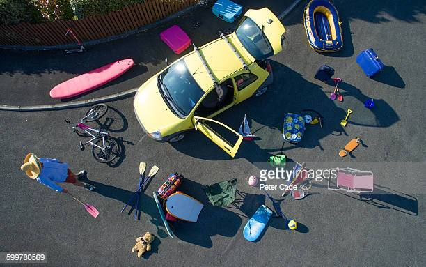 Car and holiday luggage spread out on road