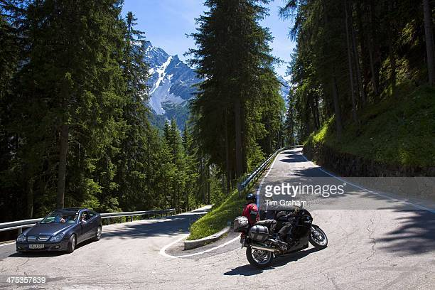 Car and motorcycle heading uphill on The Stelvio Pass Passo dello Stelvio Stilfser Joch in the Alps Italy