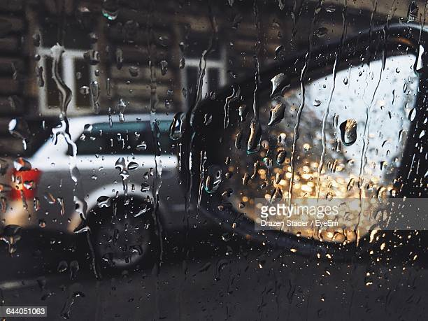 Car And Side-View Mirror Seen Through Wet Glass Window During Rainy Season