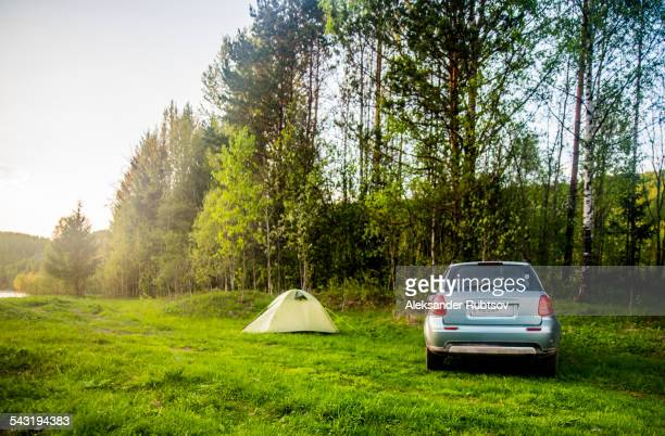 Car and tent at campsite in field