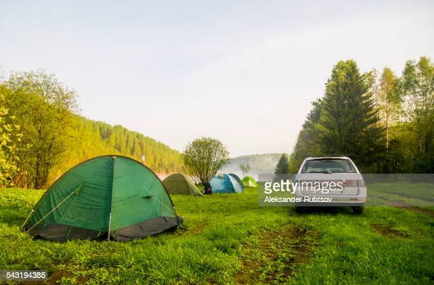 Car and tents at campsite in field