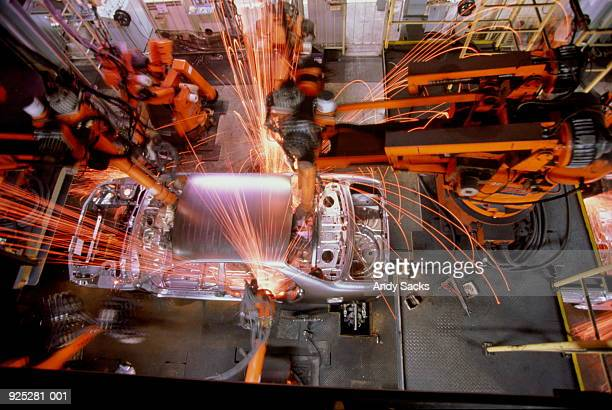 Car assembly line, robotic welding on car body, overhead view