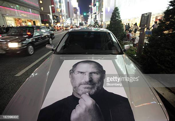 A car bearing a photograph of Steve Jobs late chief executive officer of Apple Inc is parked outside the Apple store at night in the Ginza district...