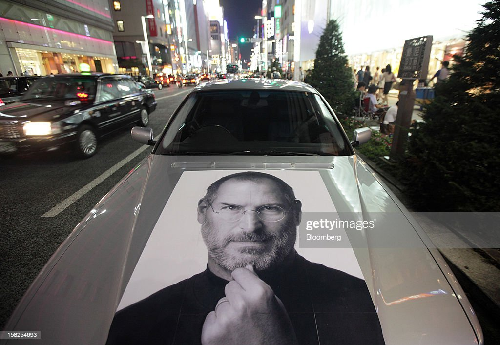 A car bearing a photograph of Steve Jobs, late chief executive officer of Apple Inc., is parked outside the Apple store at night in the Ginza district of Tokyo, Japan, on Thursday, Sept. 20, 2012. Apple's iPhone 5, which features a bigger screen, faster chip and a lighter body, sold 2 million units in first-day orders, more than double a record set by the previous model, Apple said. Photographer: Tomohiro Ohsumi/Bloomberg via Getty Images