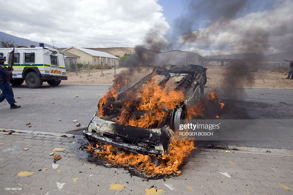 A car belonging to South African newspaper group, Independent Newspapers, burns after being set alight during clashes between striking farm workers and anti-riot police forces on January 9, 2013 in de Doorns, a small farming town about 140km north of Cape Town, South Africa. Workers on fruit farms have downed tools, demanding a wage hike from 69 rand ($8) to 150 rand ($17.50) a day. The protesters also occupied part of the country's major N1 highway, forcing dozens of police officers and two armoured vehicles to move down the road, pushing the protesters back from the town entrance.