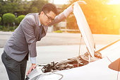 Young Asian business man looking under the hood of breakdown car.
