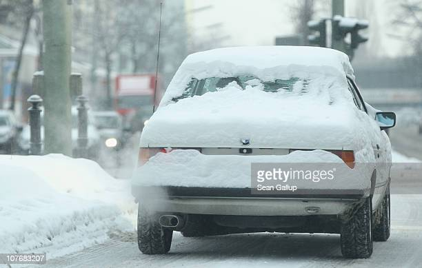A car burdened under snow drives on a frigid day in the city center on December 19 2010 in Berlin Germany Heavy snowfalls across Europe are grounding...