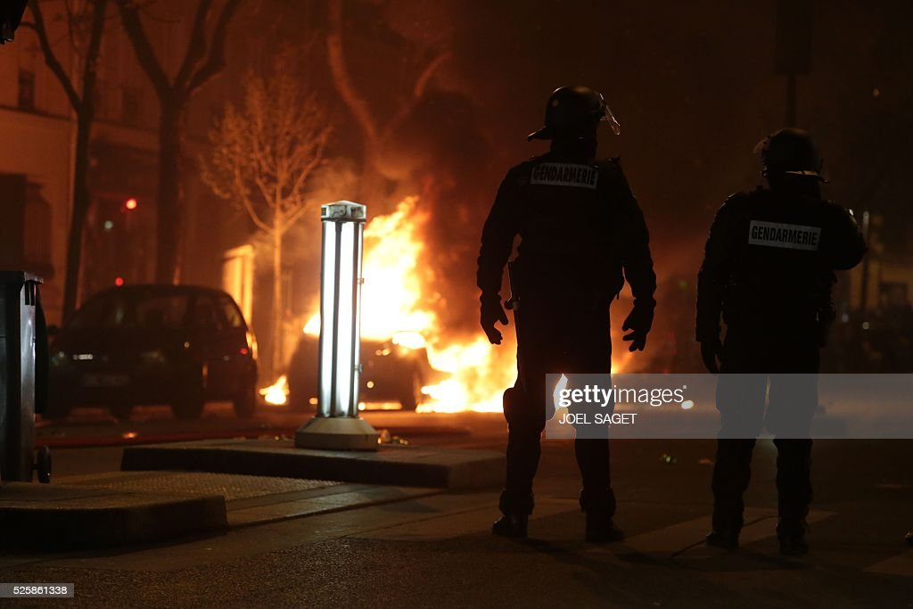 A car burns as French Gendarmerie clear the Place de la Republique during a protest by the Nuit Debout, or 'Up All Night' movement who have been rallying against the French government's proposed labour reforms early on April 29, 2016. Twenty-seven people were arrested and 24 detained during the overnight clashes in the French capital as the police dispersed the protesters who began their began movement on March 31 in opposition to the government's proposed labour reforms.