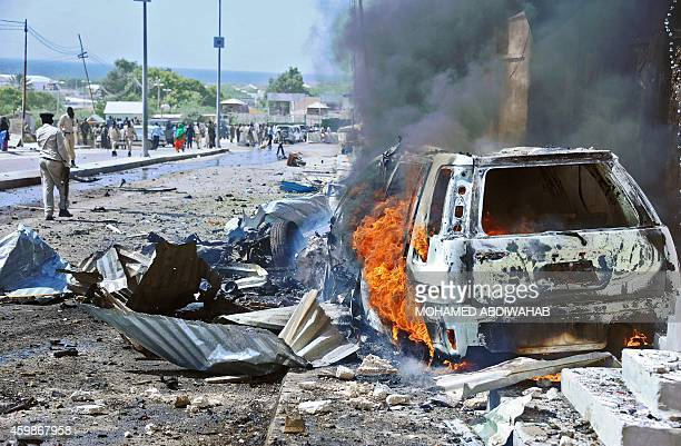 A car burns following a blast near the heavily fortified gates of the airport in Mogadishu on December 3 2014 At least four people were killed in...